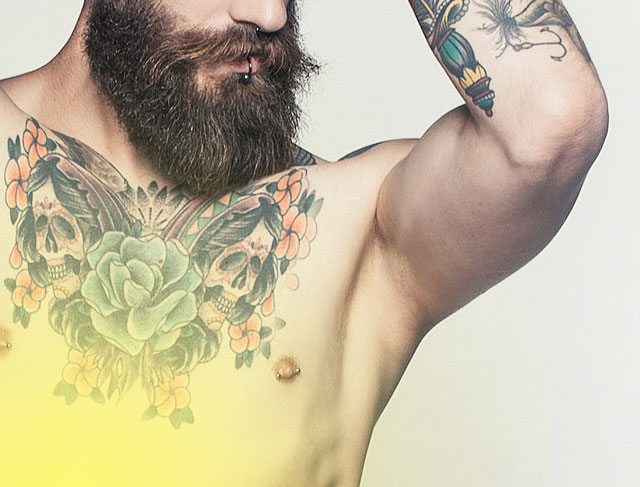 Man with beard and tattoo shows shaved underarm, removed underarm hair